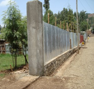 A fence built to last. Notice the stout foundation and the gutters.   This should stand up for many, many rainy seasons.