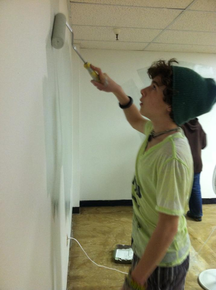 Gage painting a wall during renovation day.